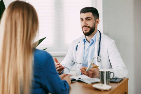 A serious male doctor of oriental appearance consults the patient, shows information about her illness and talks about the medical examination.