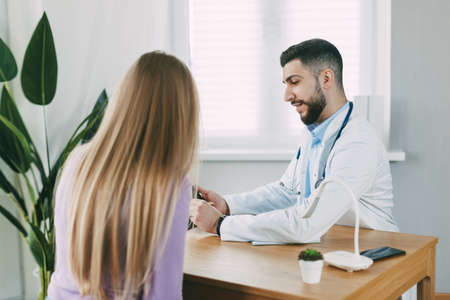 The male doctor consults the patient, shows information about his illness and talks about the medical examination.