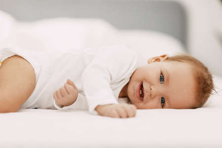 A blue-eyed baby lies in a snow-white bed under a blanket, laughs and indulges Stock fotó