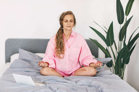 A young woman meditates while sitting on a bed with a laptop. The girl does yoga exercises at home to relieve stress, taking a break from work.