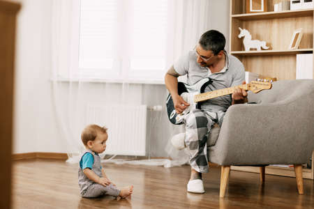 A middle-aged father with tattoos on his arms sits in an armchair in the room and plays the guitar to his little one.