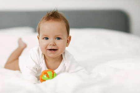The kid lies in a snow-white bed, laughs and plays with a rattle.