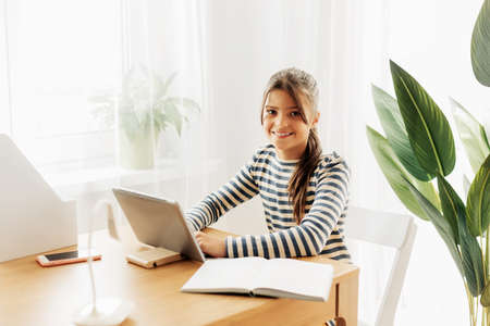 Smiling schoolgirl in a striped sweater sits at the table, does homework on the tablet and takes notes in a notebook. Modern technologies, online education, training Standard-Bild