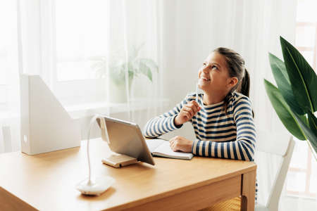 Happy pensive schoolgirl sits at the table at home, does homework on the tablet and looks out the window. Modern technologies, online education, training Standard-Bild