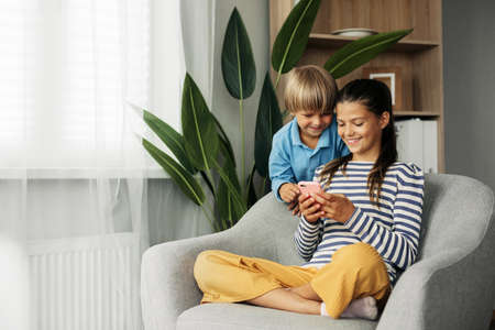 Sister and younger brother are sitting at home in an armchair and playing on the phone. Modern technology and spending time at home
