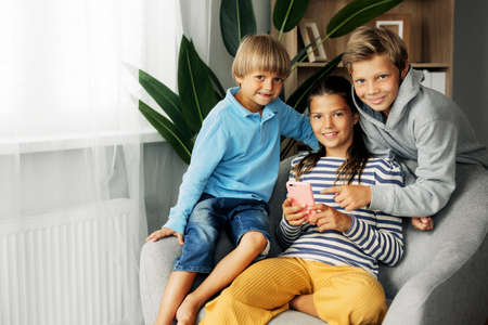 Children sit at home on the couch, play games on the phone, chat with friends. Modern technology and spending time at home