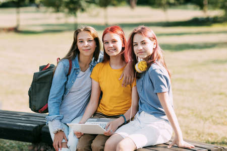 A group of teenage girls is sitting on a park bench and preparing for classes together, discussing homework and having fun. Time together, friends, friendship, training.