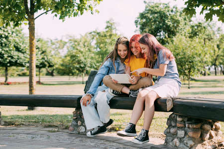 Three charming schoolgirls are sitting on a park bench and preparing for lessons or exams together. Friends, friendship, time together
