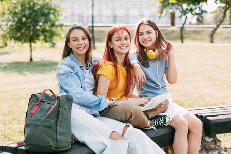 Three schoolgirls are sitting on a park bench, talking, preparing together with the lesson. The concept of training and education