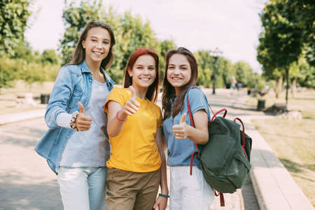 Cheerful schoolgirls walk in the park after school and show the class. The concept of friendship