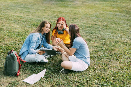 Teenage girls are sitting on a green lawn in a park with a backpack and a digital tablet and are preparing a joint project. Education and knowledge, lifestyle of teenagers