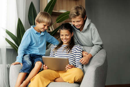 The beautiful dark-haired sister and her brothers are sitting at home on the couch, playing games on the tablet and chatting with friends via video. Modern technology and spending time at home Standard-Bild