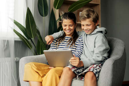 Sister and older brother are sitting at home in a chair and playing on the tablet. Modern technology and spending time at home Standard-Bild