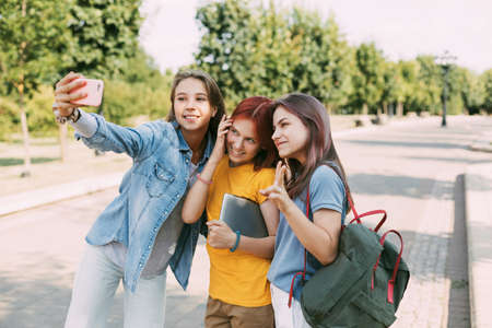 Three charming friends take selfies with their phone on the way to school. The concept of friendship. Education, training, back to school