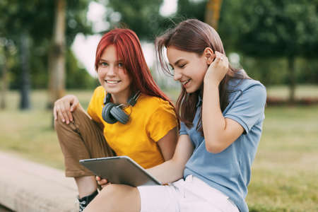 Two charming schoolgirl girlfriends are sitting in the park after school and watching videos on a tablet or preparing a joint project. Standard-Bild