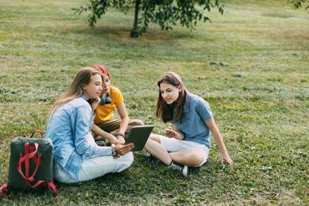 Teenage girls sit on the green lawn in the park during a break. Education and knowledge, lifestyle of teenagers Standard-Bild