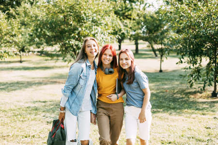 Three teenage girls are walking in the park after school. The concept of training and education. Back to school Standard-Bild