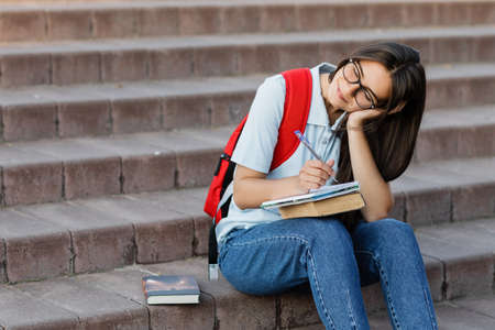 A thoughtful girl student is sitting on the stairs near the university