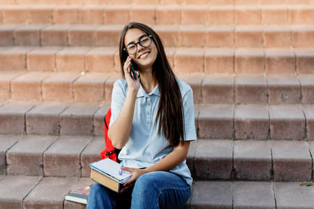 A cheerful girl is talking on a mobile phone with her friend, sitting with a notebook on the stairs in the campus