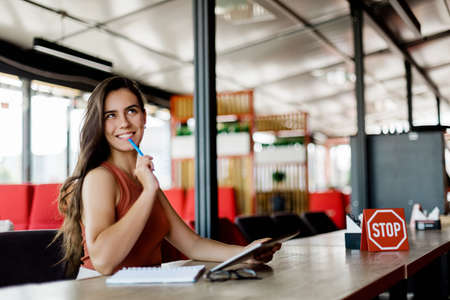A smiling girl in a cafe is studying or working using a tablet, making notes in a notebook. Standard-Bild
