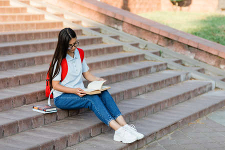 A pretty girl student in glasses, with a backpack is sitting on the stairs near the university, reading a book, preparing for lectures or exams. Training and education Standard-Bild