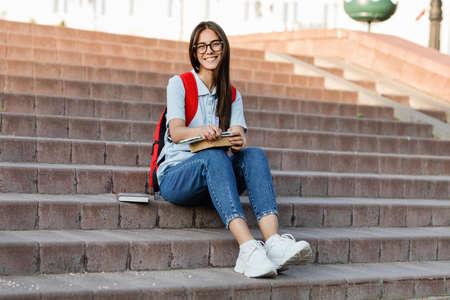 A focused student with glasses, sitting on the stairs, writes in her notebook. Preparation for a lecture or exam