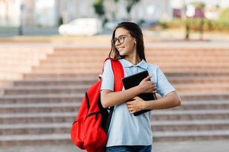 A smiling pretty student in glasses and with a red backpack, with a tablet in her hands, stands next to the stairs and smiles