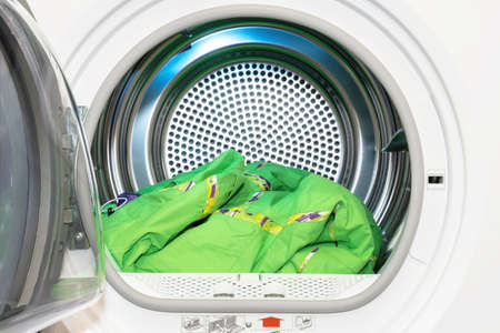 Clothes dryer with washed and dried outdoor clothes inside. Standard-Bild