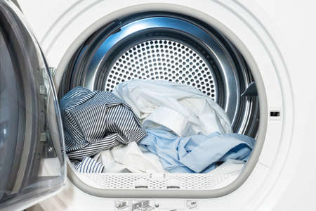 Close up view on clothes dryer with washed and dried shirts in and door open. Banco de Imagens
