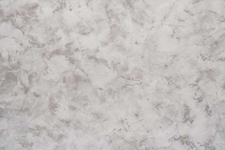 Background of light gray putty or textured gypsum plaster with white stains on the wall.