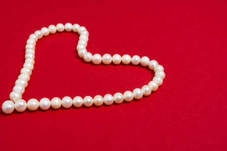 Pearl beads in the shape of a heart on red background. Valentines day or Womens day concept. Standard-Bild