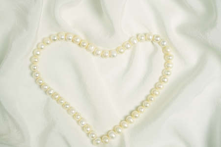 Pearl beads in the shape of heart on white silk fabric. Valentines day, womens day or wedding day background. Greeting card template