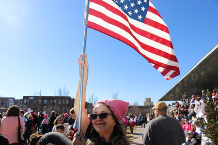 Woman with pink hat hold American flag high over crowd at Women March Tulsa Oklahoma 1-20-2018