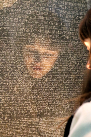 Girls face reflected as she tries to read the Rosetta Stone with writing in different ancient languages - selective focus - in British Museum London UK 1-10-2018