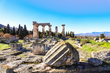 Broken columns in front of the remaining columns of the Temple of Apollo in ancient Corinth on the Peloponnese peninsula in Greece - snow covered mountians in background