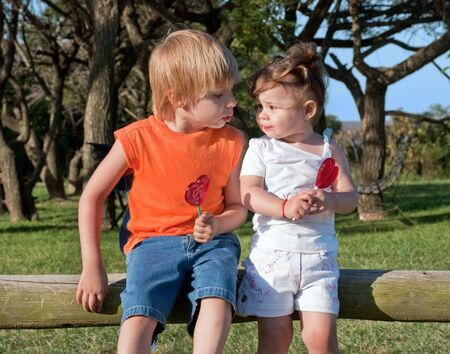 boy and girl sitting on the beam in the park with caramel photo