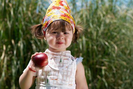 little girl eats peach in the park photo