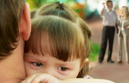 child crying on the shoulder of the adult