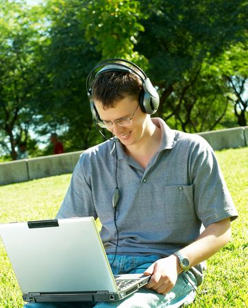 guy listens music on a laptop in the park photo