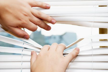 Mens hands apart on the window blinds