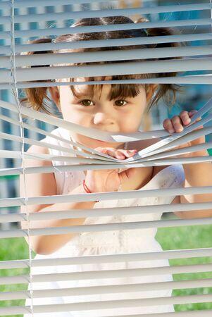 Meisje kijkend door de blinds apart hen met handen