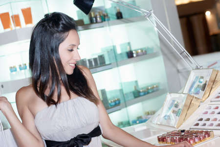 woman chooses perfume on the showcase in the shop Stock Photo - 9550829