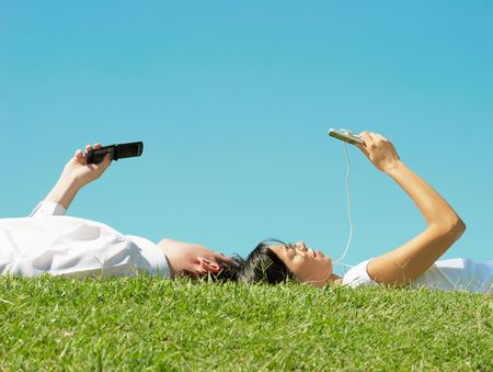man and woman lie on the grass in the park with cell photo