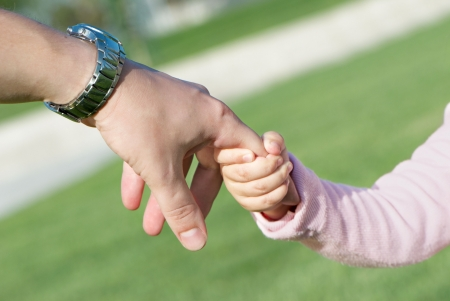 Daughter holds hand of the father Stock Photo