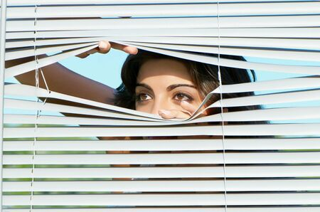 pry: girl looking through the blinds apart them with hands Stock Photo