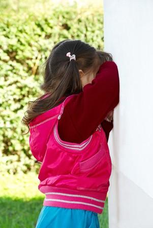 boos meisje stand tegen een muur