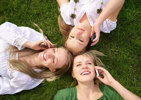 women talking:  girls talking on mobile phones in park on the grass Stock Photo