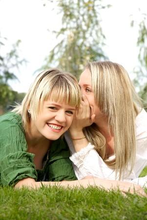 Foto van twee meisjes die splijt geheimen met elkaar