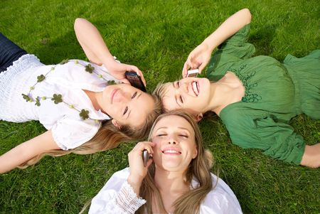 girls talking on mobile phones in park on the grass Stock Photo