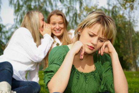 offended girl sitting on grass in the park Stock Photo